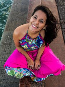 Jéssica Felipe, diretora do episódio Maria Flor, do Pense Grande.doc, usa vestido com tons de rosa. Tem cabelos castanhos e sorri