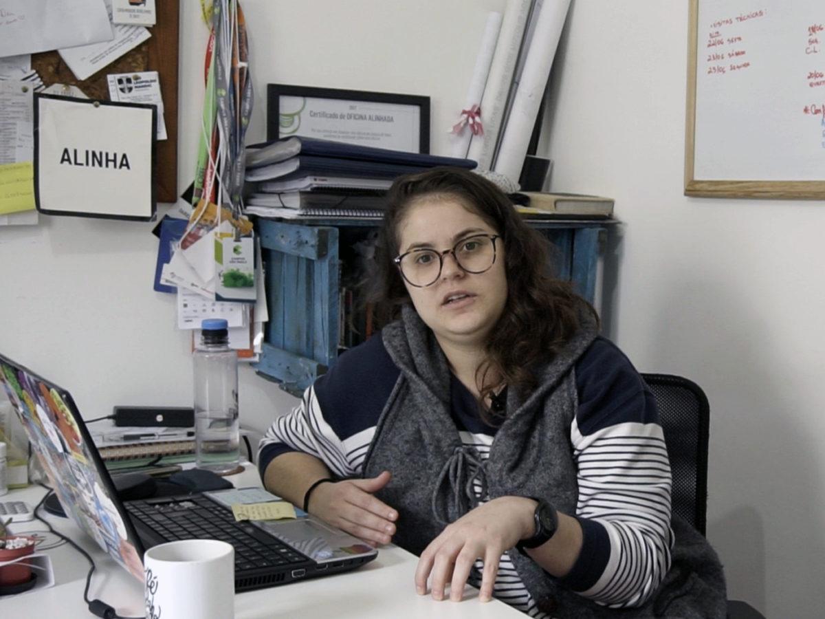 Dari Santos, fundadora do Alinha. Ela usa óculo e está sentada diante do computador