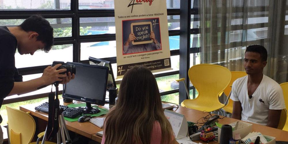 Imagem mostra homem de camiseta branca sentado à frente de uma mulher e um homem durante gravação do episódio PLT4way no Pense Grande.doc