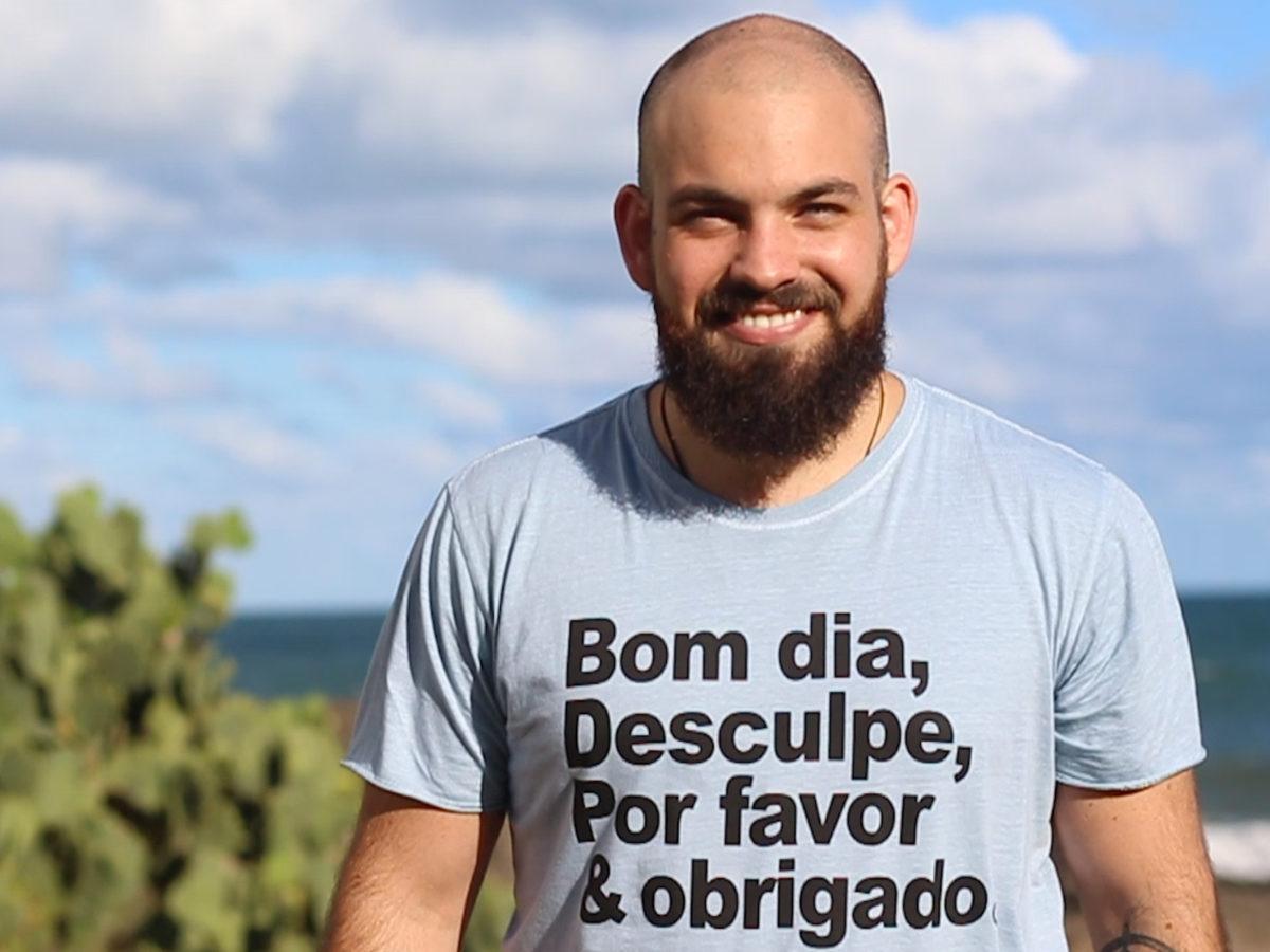 Jovem usa camiseta da marca Euzaria, onde se lê Bom dia, desculpe, por favor e obrigado