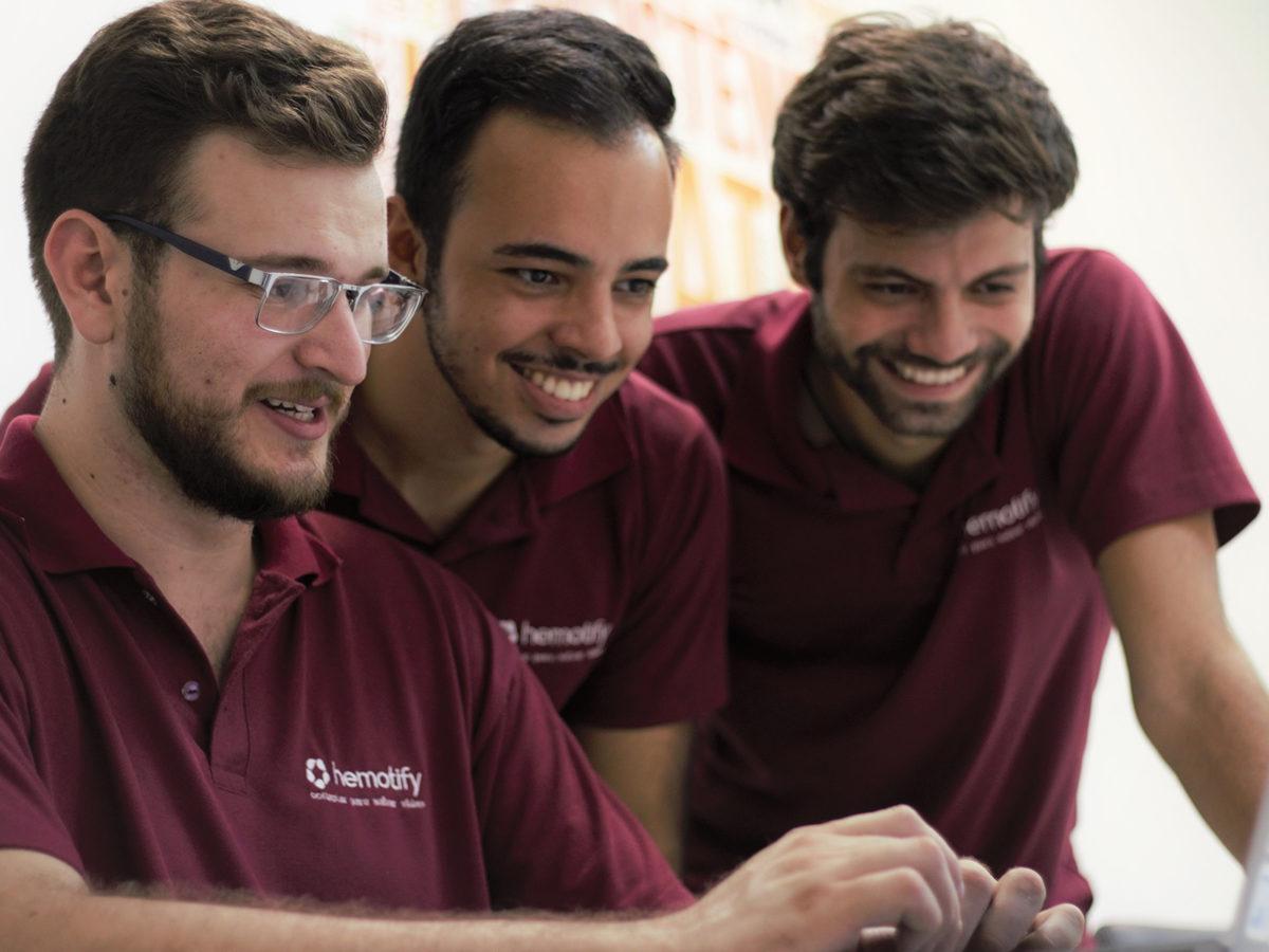 Três jovens criadores do Hemotify usam camiseta cor de vinho e sorriem na frente de um computador